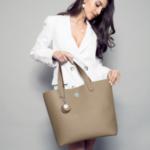 A woman holding a vegan leather fashion bag