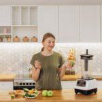 A woman standing next to a blender, vegan technology